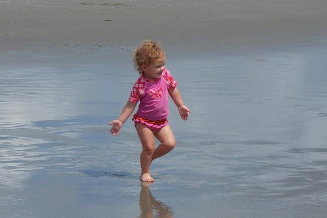 My very happy toddler dances to the ocean.